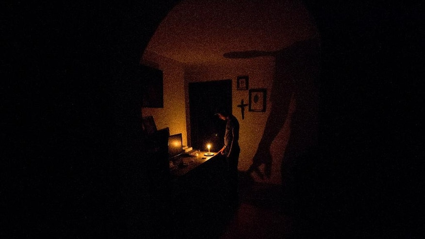 In this Saturday, April 23, 2016 photo, a boy illuminates his home with a candle during a 24-hour blackout, in the El Calvario neighborhood of El Hatillo, just outside of Caracas, Venezuela. Energy rationing has been added to the hardships faced by Venezuelans overwhelmed by inflation, shortages of food and medicine and rising crime. (AP Photo/Fernando Llano)