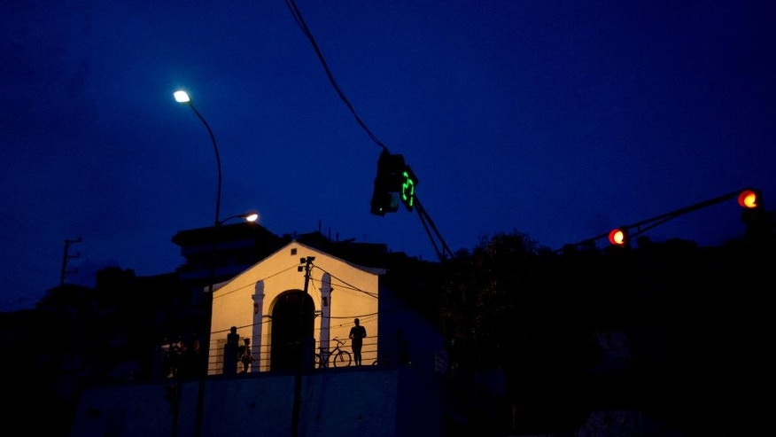 In this Saturday, April 23, 2016 photo, residents are silhouetted against the facade of a church, the only building illuminated after a 24-hour blackout, in the El Calvario neighborhood of El Hatillo, just outside of Caracas, Venezuela. Energy rationing has been added to the hardships faced by Venezuelans overwhelmed by inflation, shortages of food and medicine and rising crime. (AP Photo/Fernando Llano)