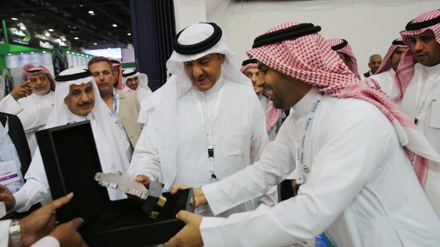 Prince Sultan bin Salman, center, receives a gift while he visits the Saudi Arabia stand at the ArabianTravel Market exhibition in Dubai, United Arab Emirates, Tuesday, April 26, 2016.  A day after Saudi Arabia outlined sweeping reform plans, the top prince spelled out for the first time in an AP interview how the kingdom aims to make tourism an important element of its shift toward less reliance on oil.  (AP Photo/Kamran Jebreili)