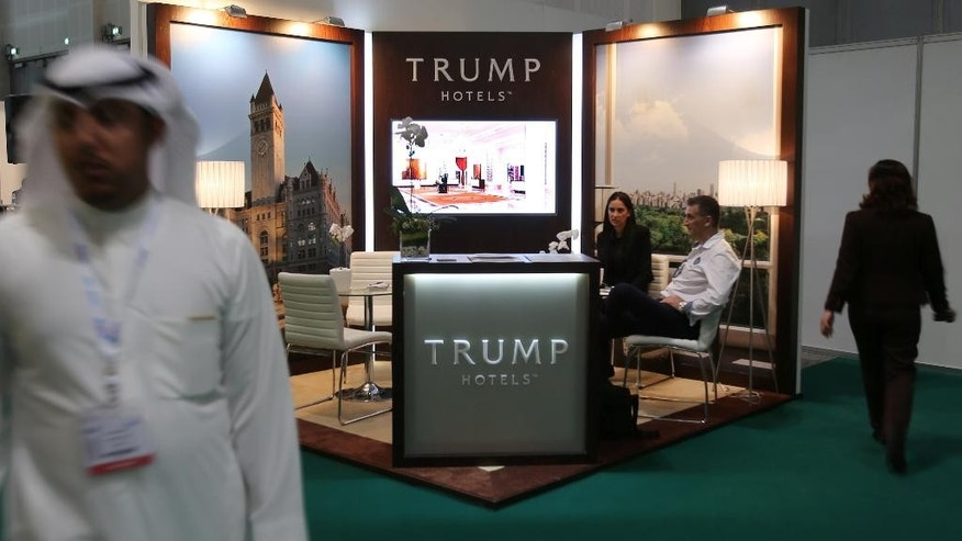 An Emirati man walks past the Trump Hotels stand at the Arabian Travel Market exhibition in Dubai, United Arab Emirates, Tuesday, April 26, 2016. Trump Hotels, the brand bearing the last name of Republican presidential candidate Donald Trump, has a stand at the Arabian Travel Market exhibition being held in Dubai, United Arab Emirates. (AP Photo/Kamran Jebreili)