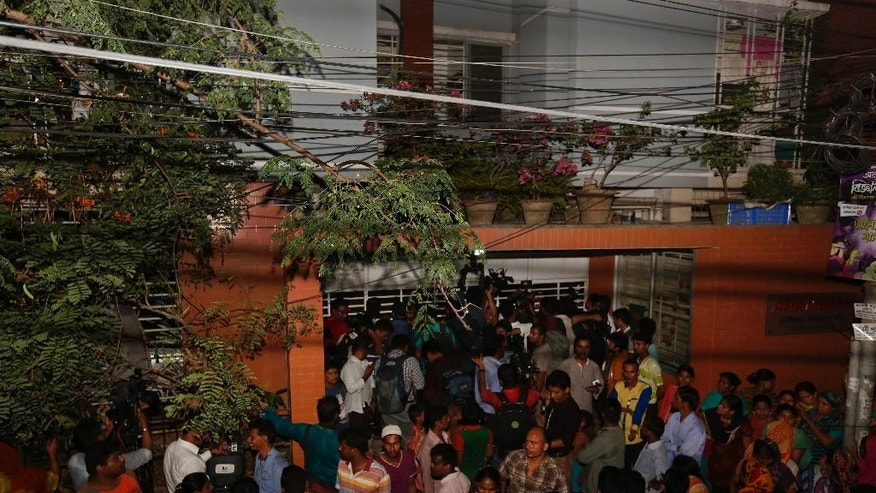 Bangladeshi people gather outside a building where two people were found stabbed to death in Dhaka, Bangladesh, Monday, April 25, 2016. Police in Bangladesh say unidentified assailants have stabbed two men to death, including a gay rights activist who also worked for the U.S. Agency for International Development.(AP Photo/A.M.Ahad)
