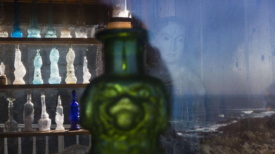 A collection of glass bottles that belonged to Chile's Nobel Prize-winning poet Pablo Neruda are displayed on the bar of his former home, now a museum, on the day he was reburied here on Isla Negra, Chile, Tuesday, April 26, 2016. Neruda's body was exhumed in 2013 for a fourth time in an effort to clear up four decades of suspicion about how the poet died in the days after Chile's military coup. The results of the analysis will be delivered on May 5. (AP Photo/Esteban Felix)