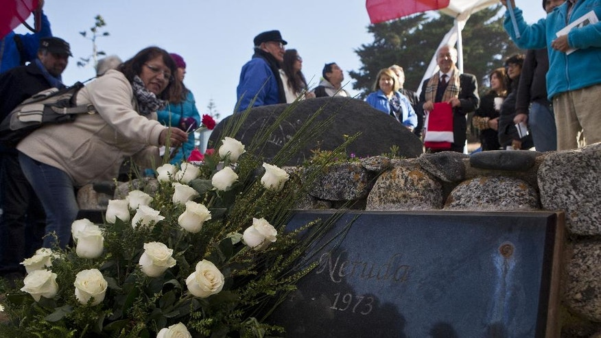 A woman places a flower on the grave of Chile's Nobel Prize-winning poet Pablo Neruda after he was reburied at his home, now a museum, on Isla Negra, Chile, Tuesday, April 26, 2016. Neruda's body was exhumed in 2013 for a fourth time in an effort to clear up four decades of suspicion about how the poet died in the days after Chile's military coup. The results of the analysis will be delivered on May 5. (AP Photo/Esteban Felix)