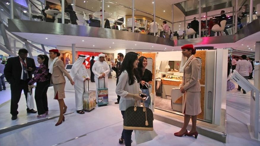 People visit the Emirates Airline stand at the ArabianTravel Market exhibition in Dubai, United Arab Emirates, Tuesday, April 26, 2016. The chairman and CEO of the long-haul airline Emirates says he's not worried about the next U.S. president being more protectionist amid an ongoing row with American carriers. (AP Photo/Kamran Jebreili)