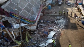 Policemen and firefighters stand on a street in the business district heavily damaged by a 7.8-magnitude earthquake, in Manta, Ecuador, Wednesday, April 20, 2016. Ecuadoreans began burying loved ones felled by the country's deadliest earthquake in decades, while hopes faded that more survivors will be found. (AP Photo/Rodrigo Abd)