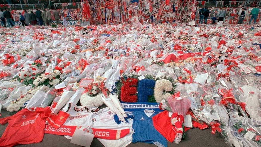 "FILE- In this file photo dated April 17, 1989, floral tributes are placed by soccer fans at the 'Kop' end of Anfield Stadium in Liverpool, England, on April 17, 1989, after the Hillsborough April 15 tragedy when fans surged forward during the Cup semi-final between Liverpool and Nottingham Forest at Hillsborough Stadium killing 96 people. The 96 Liverpool soccer fans who died in the Hillsborough Stadium disaster were ""unlawfully killed"" because of errors by the police, a jury concluded Tuesday April 26, 2016. (AP Photo/ Peter Kemp, File)"