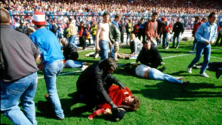 "FILE - In this April 15, 1989 file photo police, stewards and supporters tend and care for wounded supporters on the field at Hillsborough Stadium, in Sheffield, England. The 96 Liverpool soccer fans who died in the Hillsborough Stadium disaster were ""unlawfully killed"" because of errors by the police, a jury concluded Tuesday April 26, 2016. (AP Photo, File)"