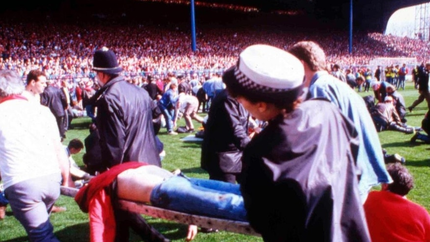 "FILE - In this April 15, 1989 file photo police, stewards and supporters tend and care for wounded supporters on the field at Hillsborough Stadium, in Sheffield, England. The 96 Liverpool soccer fans who died in the Hillsborough Stadium disaster were ""unlawfully killed"" because of errors by the police, a jury concluded Tuesday April 26, 2016.(AP Photo, File)"
