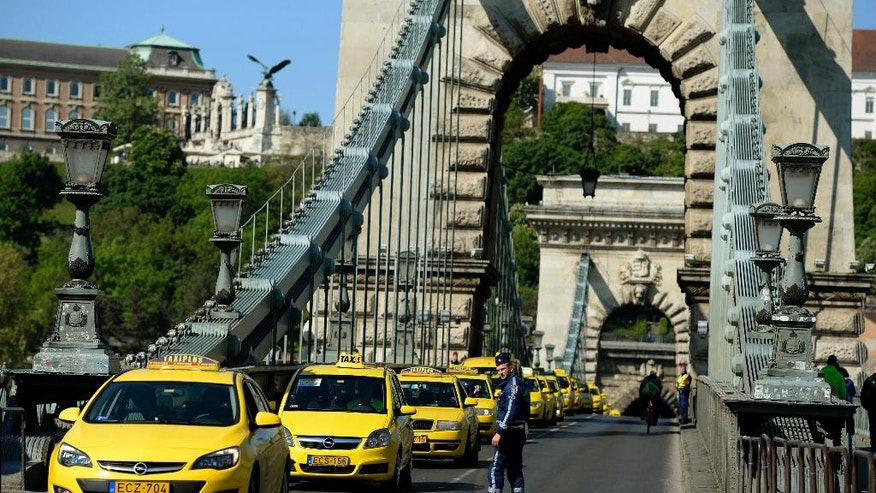 Taxi drivers line up their vehicles at Chain Bridge during their demonstration against the use of Uber rideshare application in downtown Budapest, Hungary, Tuesday, April 26, 2016. (Noemi Bruzak/MTI via AP)