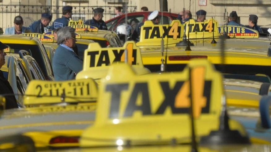 Taxi drivers line up their vehicles at Heroes' Square during their demonstration against the use of Uber rideshare application in downtown Budapest, Hungary, Tuesday, April 26, 2016. (Zoltan Mathe/MTI via AP)