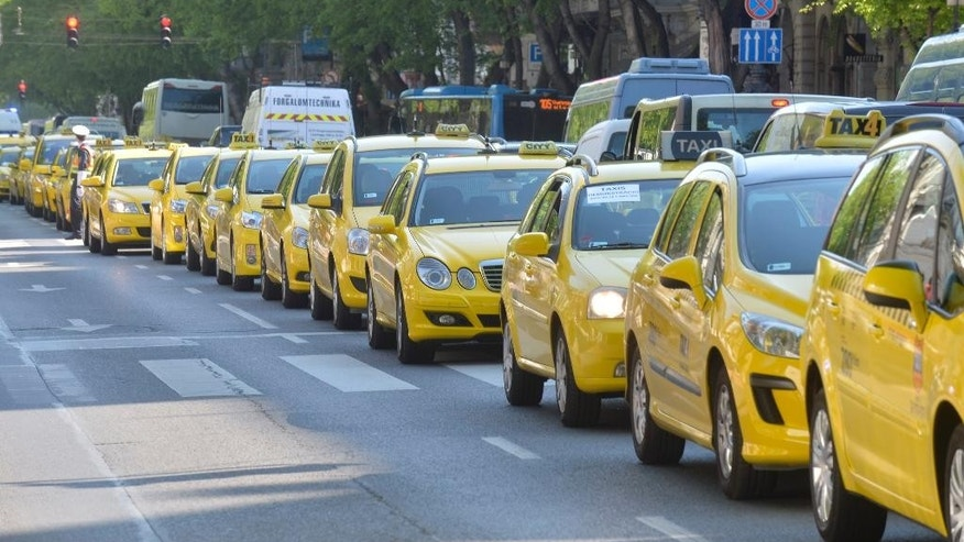 Taxi drivers line up their vehicles at Andrassy road during their demonstration against the use of Uber rideshare application in downtown Budapest, Hungary, Tuesday, April 26, 2016. (Zoltan Mathe/MTI via AP)