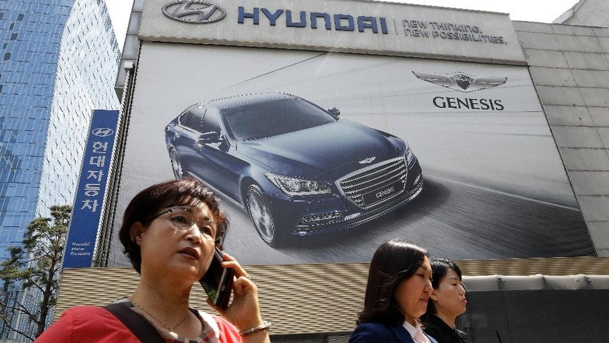 People walk under a billboard advertising Hyundai Motor Co.'s Genesis in Seoul, South Korea, Tuesday, April 26, 2016. Hyundai Motor Co. says its first-quarter net profit has dropped 12 percent over a year earlier as global sales declined. (AP Photo/Ahn Young-joon)