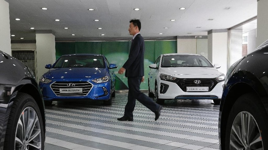An employee of Hyundai Motor Co. walks by vehicles displayed at the company's showroom in Seoul, South Korea, Tuesday, April 26, 2016. Hyundai Motor Co. says its first-quarter net profit has dropped 12 percent over a year earlier as global sales declined.(AP Photo/Ahn Young-joon)