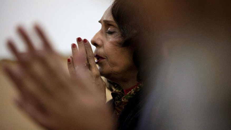 In this Jan. 17, 2016 photo, an Indian woman chants Buddhist prayers in New Delhi, India. Chanting Buddhist mantras is catching on among India's urban elite as a way to relieve stress. Most are Hindu, but they don't see a conflict between their religious beliefs and the chanting, which some find soothing, others invigorating. The practice seems to be growing mostly by word of mouth, with practitioners chanting daily and getting together for monthly chanting sessions in various locations. (AP Photo/Tsering Topgyal)