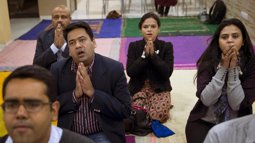 In this Jan. 17, 2016 photo, Ruma Roka, second from right, who runs an institute for young people with hearing impairment, joins a Buddhist chanting session in New Delhi, India. Chanting Buddhist mantras is catching on among India's urban elite as a way to relieve stress. Most are Hindu, but they don't see a conflict between their religious beliefs and the chanting, which some find soothing, others invigorating. Roka feels that she would have a compassion deficit and would not be able to survive with her challenging work if she did not take up Buddhist chanting. (AP Photo/Tsering Topgyal)