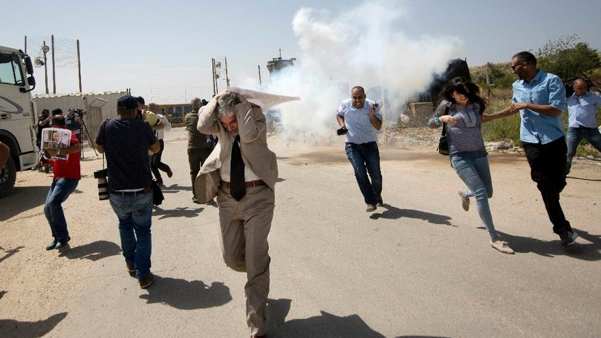 Palestinian journalists run from tear gas fired by Israeli troops during a protest calling for the release of Palestinian journalist Omar Nazzal, who was arrested by Israeli authorities over the weekend, outside Ofer military prison near the West Bank city of Ramallah, Tuesday, April 26, 2016. (AP Photo/Majdi Mohammed)