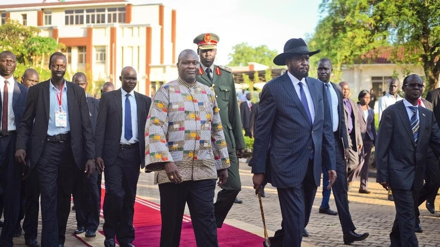 South Sudan's rebel leader and now Vice President Riek Machar, center-left, walks with President Salva Kiir, center-right, after being sworn in at the presidential palace in the capital Juba, South Sudan Tuesday, April 26, 2016. Machar returned to the capital Tuesday to become vice president and to try to end the civil war that in two and a half years has killed tens of thousands of people and forced more than 2 million from their homes. (AP Photo/Jason Patinkin)