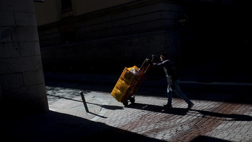 A deliveryman pushes a trolley with goods in Madrid, Tuesday, April 26, 2016. Spain's king is wrapping up two days of talks with political party leaders in a last-ditch bid to snap a four-month deadlock in finding a candidate capable of forming a government, but another election looks more likely. (AP Photo/Francisco Seco)