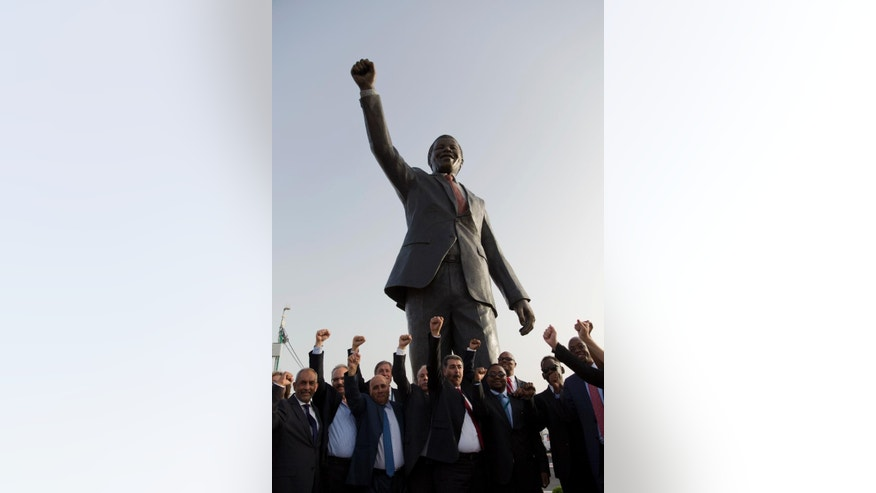 Palestinians pose for a memorial picture with a sculpture of the first democratically elected South African president and anti apartheid leader Nelson Mandela, in the West Bank city of Ramallah, Tuesday, April 26, 2016. Palestinians honored Mandela unveiling his statue on a square in Ramallah, on South Africa's Freedom Day that is observed annually to commemorate the first post apartheid elections held on April 27, 1994. (AP Photo/Nasser Nasser)