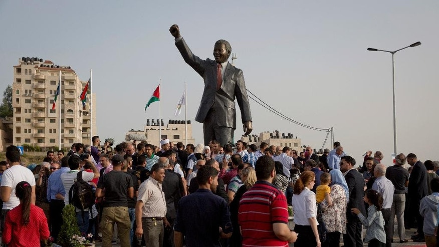Palestinians take part in ceremony to unveil a sculpture of the first democratically elected South African president and anti apartheid leader Nelson Mandela, in the West Bank city of Ramallah, Tuesday, April 26, 2016. Palestinians honored Mandela unveiling his statue on a square in Ramallah, on South Africa's Freedom Day that is observed annually to commemorate the first post apartheid elections held on April 27, 1994. (AP Photo/Nasser Nasser)
