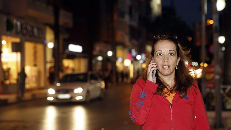Dutch-Turkish journalist Ebru Umar talks on her mobile phone in Kusadasi, Turkey, Monday, April 25, 2016. Umar, a columnist for The Netherlands' Metro newspaper, has been barred from leaving Turkey as authorities continue to investigate whether she should be charged for two of her tweets that were deemed offensive to Turkey's President Recep Tayyip Erdogan.(AP Photo)