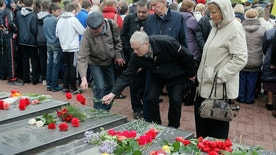 Ukrainians lay flowers to the tombstone that bears their relative's names, during a ceremony to commemorate victims of Chernobyl tragedy at a monument to them in Ukraine's capital Kiev, Ukraine, Tuesday, April 26, 2016. Ukraine marks the 30th anniversary of the Chernobyl nuclear disaster, which spread radiation over much of northern Europe. (AP Photo/Efrem Lukatsky)
