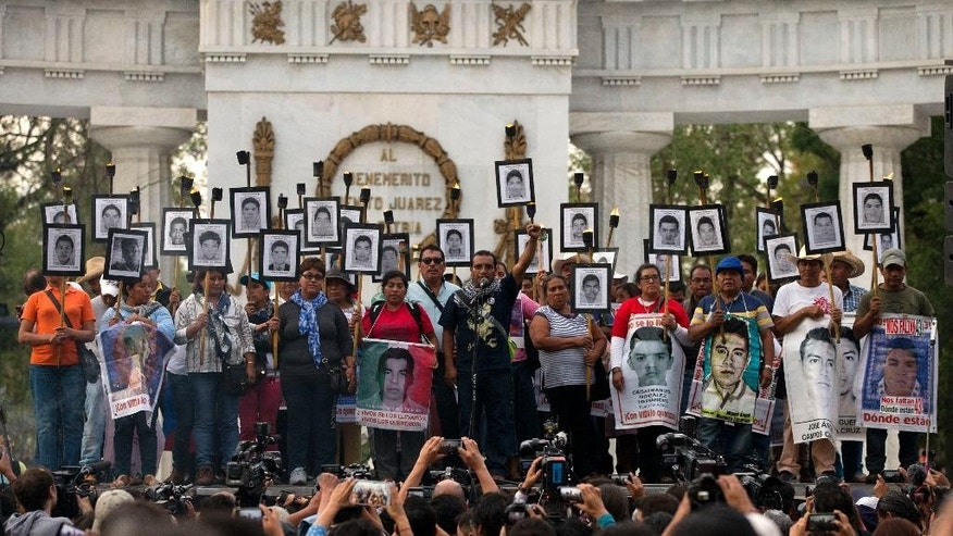 Family members of 43 missing teachers college students carry pictures of the students as they protest to demand the case not be closed and that experts' recommendations about new leads be followed, in Mexico City, Tuesday, April 26, 2016. The U.N. Office of the High Commissioner for Human Rights said Tuesday that it is troubled by a group of international experts' complaints of obstacles to their investigation into Sept. 26, 2014 disappearance of the students in southern Guerrero State.(AP Photo/Rebecca Blackwell)