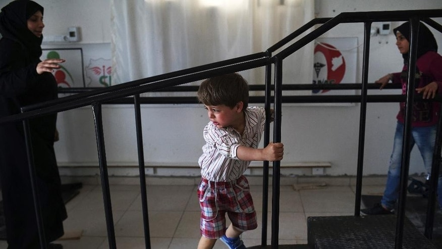 Three-year-old Seif, last name not available, using his two new prosthetic limbs, attends a rehabilitation session at a clinic in the Turkish border town of Reyhanli, where hundreds of wounded Syrians come in every week to receive prosthetic limbs, Wednesday, April 20, 2016. Seif lost his legs after a rocket hit the car in the Syrian city of Aleppo he and his family were driving in.  (AP Photo/Bram Janssen)