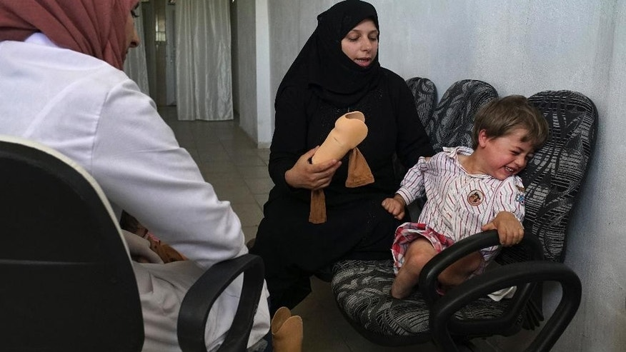 Three-year-old Seif, last name not available, cries as his mother tries to put on one of his two new prosthetic limbs during a rehabilitation session at a clinic in the Turkish border town of Reyhanli, where hundreds of wounded Syrians come in every week to receive prosthetic limbs, Wednesday, April 20, 2016. Seif's daily training routine starts with tears but ends in burst of laughter as he takes his first steps with the help of his mother. Seif lost his legs after a rocket hit the car in the Syrian city of Aleppo he and his family were driving in. (AP Photo/Bram Janssen)