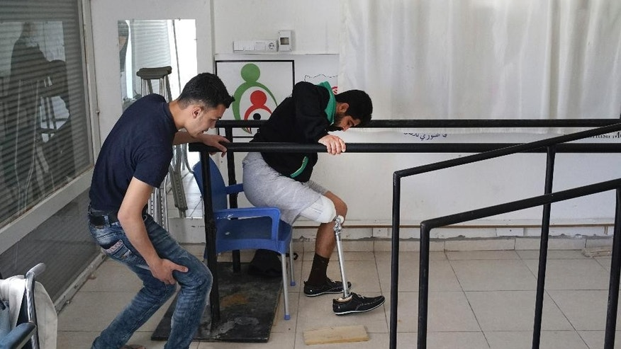 Syrian Mahmoud Shamoo, left, a technician and therapist helps a Syrian patient, who didn't want to be identified, with his first steps on his new prosthetic limb at a clinic in the Turkish border town of Reyhanli, where hundreds of wounded Syrians come in every week to receive prosthetic limbs, Wednesday, April 20, 2016. Treatment at the clinic is for free and only for Syrian civilians and fighters who lost their limbs in the war in their home country.  (AP Photo/Bram Janssen)