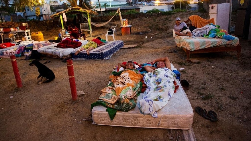 In this Wednesday, April 20, 2016 photo, neighbors Carlos Bardales, left, and Cesar Filay, share a mattress as they sleep outside their collapsed homes damaged by a 7.8-magnitude earthquake, in Manta, Ecuador. Hundreds of aftershocks have rattled the country since last Saturday night's quake and Ecuadoreans are still sleeping outside and struggling to find food and water. (AP Photo/Rodrigo Abd)