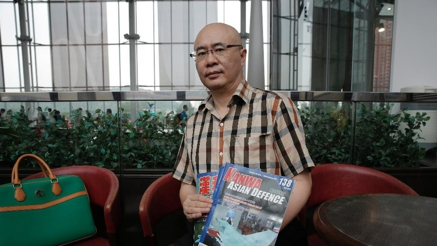 Kanwa Asian Defense publisher Andrei Chang poses with his magazines in Hong Kong, Thursday, April 28, 2016. The publisher of a leading magazine on Chinese and regional defense issues says he's leaving Hong Kong out of concern he could be targeted by China's state security bodies, a further sign of how Beijing's growing presence is chilling the political atmosphere in the territory. (AP Photo/Kin Cheung)