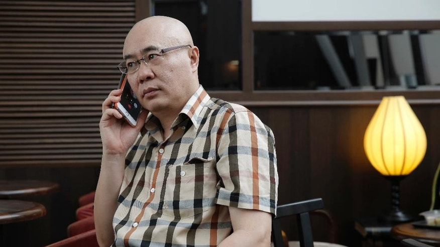 Kanwa Asian Defense publisher Andrei Chang talks on phone in Hong Kong, Thursday, April 28, 2016. The publisher of a leading magazine on Chinese and regional defense issues says he's leaving Hong Kong out of concern he could be targeted by China's state security bodies, a further sign of how Beijing's growing presence is chilling the political atmosphere in the territory. (AP Photo/Kin Cheung)