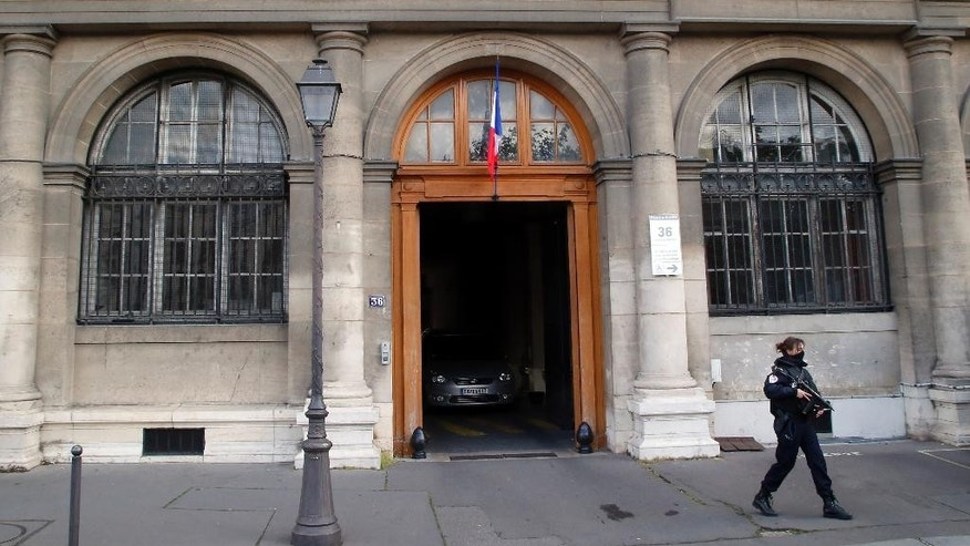 A police officer guards the entrance of the judicial Police headquarters, part of the Palace of Justice complex, in Paris, France, Wednesday, April 27, 2016. The French prosecutor's office said that key Paris attacks suspect Salah Abdeslam was transferred to France Wednesday morning and was to go before investigating judges for eventual charges. (AP Photo/Michel Euler)