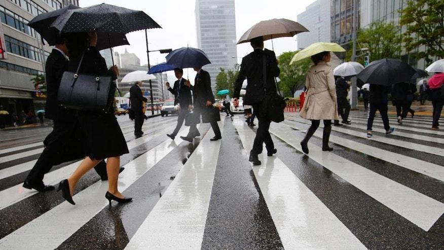 People walk on a pedestrian crossing in Tokyo, Thursday, April 28, 2016.  Japan's central bank opted Thursday not to expand its massive stimulus policies to boost growth, apart from channeling extra support for financing disaster recovery efforts on the earthquake-stricken southern island of Kyushu. (AP Photo/Shizuo Kambayashi)