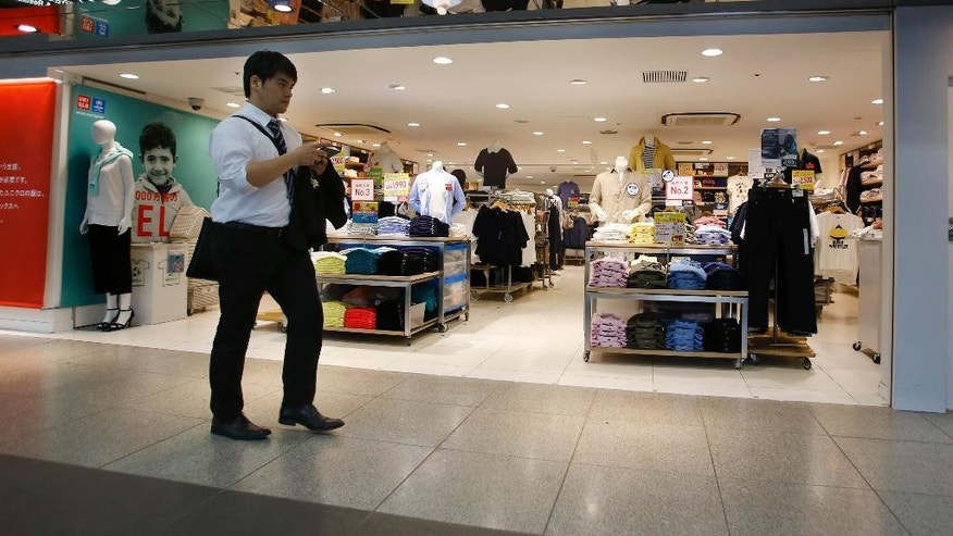 A man walks in front of a clothing store in Tokyo, Thursday, April 28, 2016.   Japan's central bank opted Thursday not to expand its massive stimulus policies to boost growth, apart from channeling extra support for financing disaster recovery efforts on the earthquake-stricken southern island of Kyushu. (AP Photo/Shizuo Kambayashi)