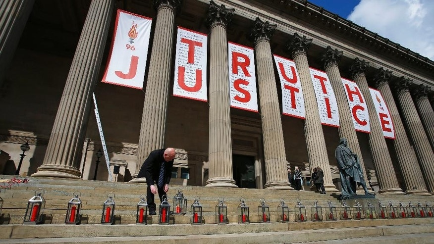A man places candles for each of the 96 Liverpool fans who died as a result of the Hillsborough disaster at St George's Hall in Liverpool, England, Wednesday, April 27, 2016. Liverpool is commemorating the deaths of 96 soccer fans crushed to death in a crowded stadium in 1989 after a jury found that blunders by police and emergency services contributed to their deaths. (Peter Byrne/PA via AP) UNITED KINGDOM OUT