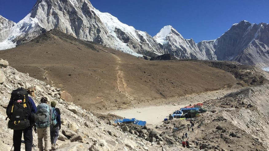 This April 10, 2016 photo shows trekkers heading to Everest Base Camp, Nepal. The cone-shaped Pumo Ri peak (23,495 feet (7,161 meters) is seen in the background. A trek to Everest Base Camp along mountain paths that hug deep gorges offers renewal and a test of mental and physical limits. Along the way there are sore knees and altitude sickness, but the spectacular landscapes, friendly villagers and moments of tranquility make the journey an unforgettable experience. (AP Photo/Karin Laub)