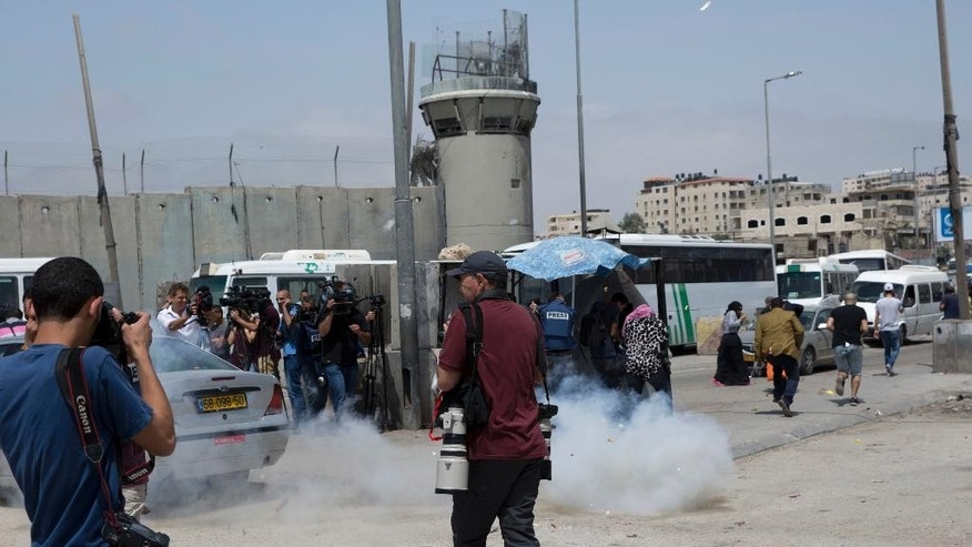 Journalists react to stun grenades, thrown by Israeli army soliders to disperse them, while they covering the news outside the Qalandia checkpoint, a main crossing point between Jerusalem and the West Bank city of Ramallah, Wednesday, April 27, 2016. Israeli security forces shot and killed two young Palestinians, including a woman, who attempted to carry out a stabbing attack at the Qalandia checkpoint, Israeli police said. (AP Photo/Nasser Nasser)