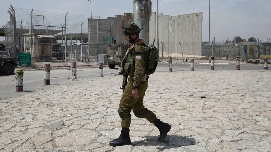 An Israeli army soldier patrols the parameter of the Qalandia checkpoint, a main crossing point between Jerusalem and the West Bank city of Ramallah, Wednesday, April 27, 2016. Israeli security forces shot and killed two young Palestinians, including a woman, who attempted to carry out a stabbing attack at the Qalandia checkpoint, Israeli police said. (AP Photo/Nasser Nasser)