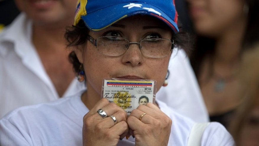 A woman holding her ID card waits in line to sign a petition that aims to initiate a recall referendum against Venezuela's President Nicolas Maduro in San Cristobal, Venezuela, Wednesday, April 27, 2016. Maduro's approval rating has plummeted amid spiraling triple-digit inflation, a deep recession and widespread shortages. (AP Photo/Fernando Llano)