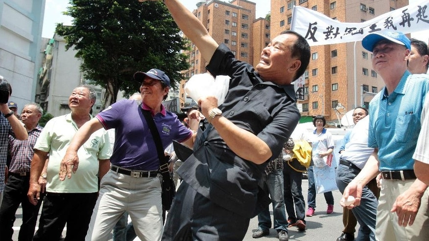 In protest of the Japanese coast guard recently detaining a Taiwanese fishing boat, fishermen hurl eggs outside of the Japan representative office in Taipei, Taiwan, Wednesday, April 27, 2016. Scores of Taiwanese fishermen protested Wednesday outside Japan's representative office in Taiwan to demand an apology over the seizure of one of their fishing boats by the Japanese coast guard. (AP Photo/ Chiang Ying-ying)
