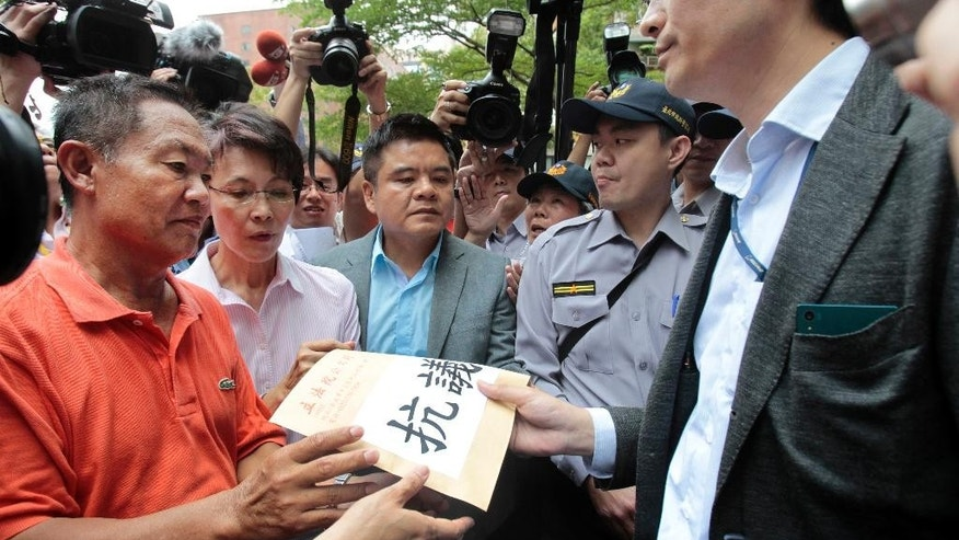 Pan Chiu-chung, left, father of detained Taiwanese fishing boat captain Pan Chien-peng, hands over a protest letter to a Japanese officer outside of the Japan representative office  in Taipei, Taiwan, Wednesday, April 27, 2016. Scores of Taiwanese fishermen protested Wednesday outside Japan's representative office in Taiwan to demand an apology over the seizure of one of their fishing boats by the Japanese coast guard. (AP Photo/ Chiang Ying-ying)