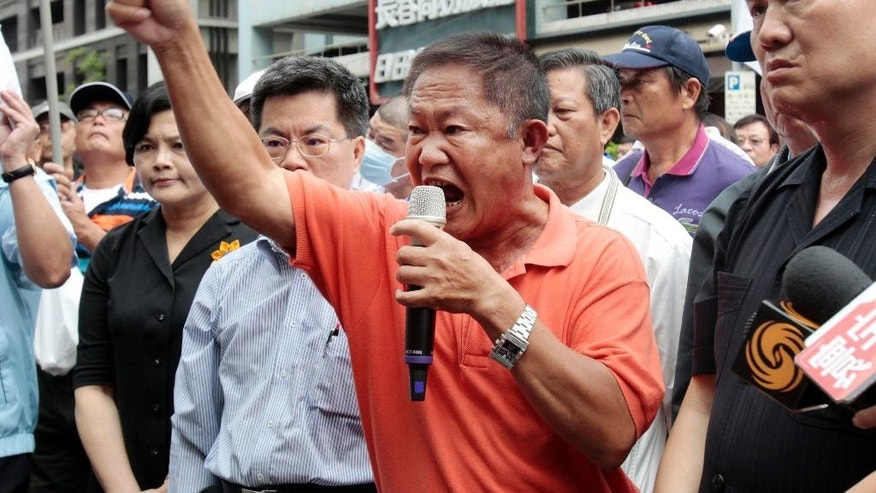 Pan Chiu-chung, center, father of a detained Taiwanese fishing boat captain Pan Chien-peng, condemns Japan during an anti-Japan protest, Wednesday, April 27, 2016 in Taipei, Taiwan. Scores of Taiwanese fishermen protested Wednesday outside Japan's representative office in Taiwan to demand an apology over the seizure of one of their fishing boats by the Japanese coast guard. (AP Photo/ Chiang Ying-ying)