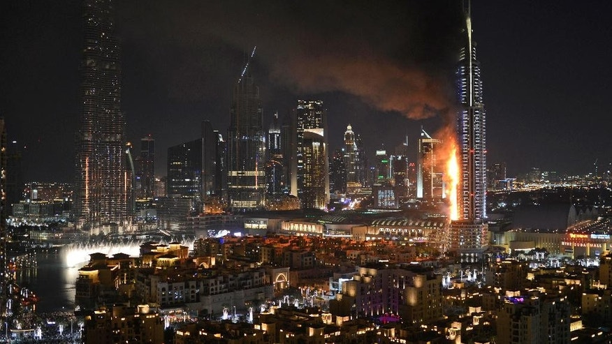 FILE- In this Thursday, Dec. 31, 2015 file photo, smoke and flames pouring from the Address Downtown Hotel in Dubai, United Arab Emirates. Officials in the United Arab Emirates are pondering how to change the country's fire safety laws after a series of skyscraper fires, including a dramatic New Year's Eve blaze seen around the world. (Sina Bahrami/@dearsina via AP, File) MANDATORY CREDIT