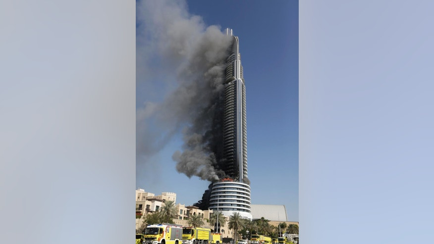 FILE- In this Friday, Jan. 1, 2016 file photo, a fire burns on the Address Downtown skyscraper in Dubai, United Arab Emirates. Officials in the United Arab Emirates are pondering how to change the country's fire safety laws after a series of skyscraper fires, including a dramatic New Year's Eve blaze seen around the world. (AP Photo/Sunday Alamba, File)