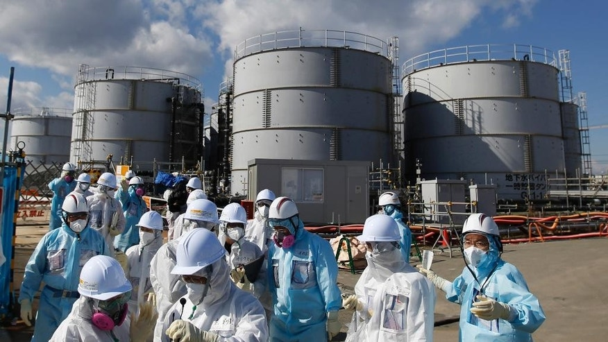"FILE - In this Feb. 10, 2016, file photo, members of a media tour group wearing a protective suit and a mask walk together after they receive a briefing from Tokyo Electric Power Co. employees (in blue) in front of storage tanks for radioactive water at the tsunami-crippled Fukushima Dai-ichi nuclear power plant in Okuma, Fukushima Prefecture, northeastern Japan. In an AP interview, a chief architect of an ""ice wall"" being built into the ground around the broken Fukushima nuclear plant defends the project but acknowledges it won't be watertight, and as much as 50 tons of radiated water will still accumulate each day. TEPCO, the utility that operates the facility, resorted to the $312 million frozen barrier after it became clear that something had to be done to stem the flow of water into and out of the broken reactors so that they can be dismantled. (Toru Hanai/Pool Photo via AP, File)"
