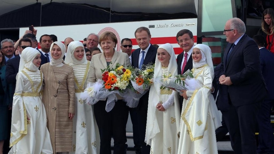 German Chancellor Angela Merkel, center-left, EU Council President Donald Tusk, center-right, Turkish Prime Minister Ahmet Davutoglu, second right, and EU Commission Vice President Frans Timmermans, right, are greeted by Syrian refugee children at a Syrian refugee camp in Nizip, Gaziantep, Turkey, Saturday, April 23, 2016. Merkel and top European Union officials, under pressure to reassess a migrant deportation deal with Turkey, were traveling close to Turkey's border with Syria on Saturday in a bid to bolster the troubled agreement. Davutoglu's wife Sare Davutoglu is at the left. (Hakan Goktepe/Pool Photo via AP)