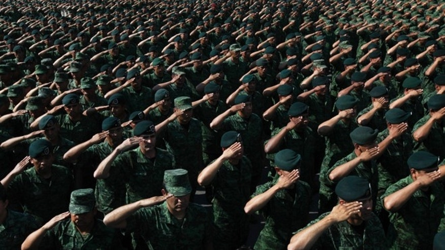 FILE - In this April 16, 2016, file photo, Soldiers salute Mexico's Defense Secretary Gen. Salvador Cienfuegos Zepeda at the Number 1 military camp in Mexico City. Cienfuegos formally apologized to the country for a video-recorded incident of torture involving two soldiers and a federal police officer. Mexican authorities have issued arrest warrants on Tuesday, April 19, for five security agents in connection with the torture of a young woman that was caught on the video. (AP Photo/Marco Ugarte, File)