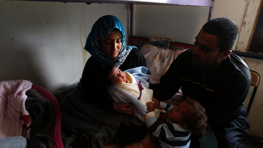 "Jaafar Al Mustafa, right, and his wife Rasmyah, left, sit in their room with his daughter Sarah and baby named Serbia Merkel in the ""Krnjaca"" collective centre, in Belgrade, Serbia, Thursday, April 28, 2016. The Al-Mustafa family is among hundreds of migrants stuck in Serbia after the official closure of the Balkan route for passage. But, the most popular track that saw one million people reach Western Europe last year, seems to be picking up in pace once again _ and the family of four has high hopes of reaching their dream location soon. (AP Photo/Darko Vojinovic)"